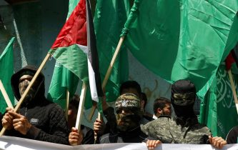 Masked Hamas militants wave green Islamic flags during a rally in solidarity with fellow Palestinians in Jerusalem and against Palestinian President Mahmoud Abbas decision to postpone Palestinian elections, in Jebaliya refugee camp, Gaza Strip, Friday, April 30, 2021. (AP Photo/Adel Hana)