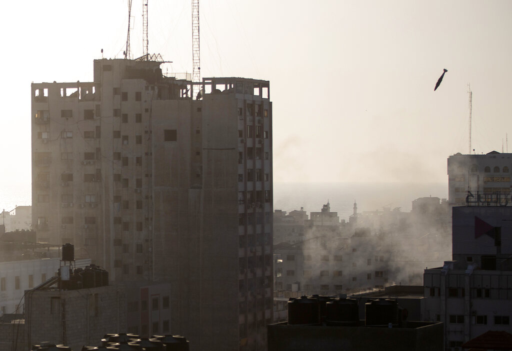 An Israeli missile flies down to hit a building in Gaza City, Wednesday, May 12, 2021. The Israeli airstrike was the latest in a series of assaults on targets in the Gaza Strip after a long dispute between Israel and Hamas erupted into an exchange of rocket attacks from Gaza and Israeli retaliation. (AP Photo/Khalil Hamra)