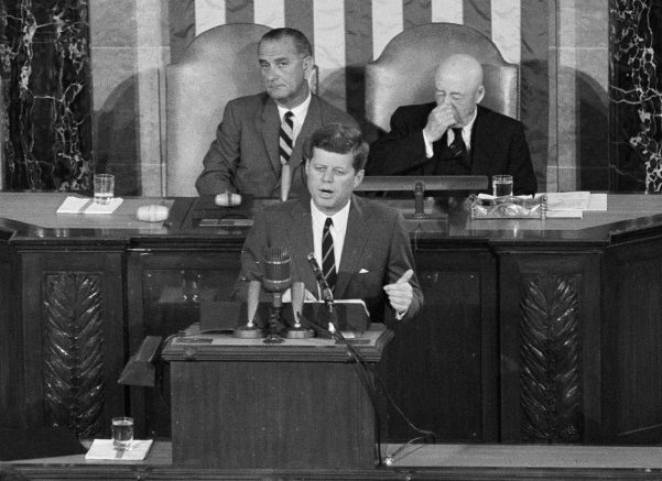 In this May 25, 1961 file photo, President John F. Kennedy speaks in the House of Representatives before a joint session of Congress in Washington. In the background are Vice President Lyndon B. Johnson, left, and House Speaker Sam Rayburn. During that speech, Kennedy issued the challenge for NASA to send a man to the moon. That challenge that was met on July 20, 1969, when Apollo 11's lunar module landed on the moon. (AP Photo, File)