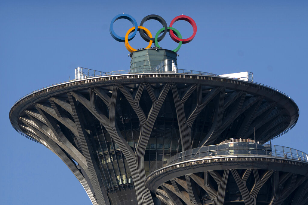 """FILE - In this Feb. 2, 2021, file photo, the Olympic rings are visible atop the Olympic Tower in Beijing. Groups alleging human-rights abuses in China are calling for a full boycott of the Beijing Olympics, which is sure to ratchet up pressure on the International Olympic Committee, athletes, sponsors, and sports federations. A coalition of activists representing Uyghurs, Tibetans, residents of Hong Kong and others, issued a statement Monday, May 17, 2021 calling for the """"full boycott,"""" eschewing lesser measures like """"diplomatic boycotts"""" and negotiations with the IOC or China. (AP Photo/Mark Schiefelbein, File)"""