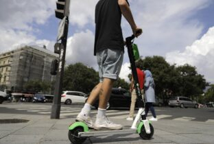 File - A man is seen riding an electric scooter. (AP Photo/Lewis Joly)