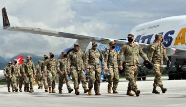 """US soldiers disembark the Boeing 747-400 """"Atlas Air"""" upon their arrival at Sarajevo International Airport on May 15, 2021. - American soldiers arrived in Sarajevo on a civilian plane from the USA, flying over Germany, and were immediately escorted by members of the Military Police of the Armed Forces of Bosnia and Herzegovina to the training ground of the AF BiH Manjaca. A total of about 500 members of the AF BiH and about 700 American soldiers will participate in the exercise """"Quick Response 21"""" at the Glamoc, Manjaca training grounds and the barracks and Dubrava airport near Tuzla. (Photo by ELVIS BARUKCIC / AFP) (Photo by ELVIS BARUKCIC/AFP via Getty Images)"""