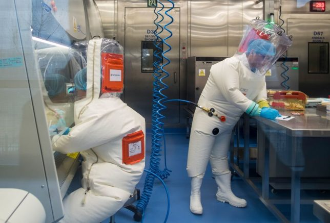 Workers are seen next to a cage with mice (R) inside the P4 laboratory in Wuhan, capital of China's Hubei province, on February 23, 2017. - The P4 epidemiological laboratory was built in co-operation with French bio-industrial firm Institut Merieux and the Chinese Academy of Sciences. (Photo by Johannes EISELE / AFP) (Photo by JOHANNES EISELE/AFP via Getty Images)