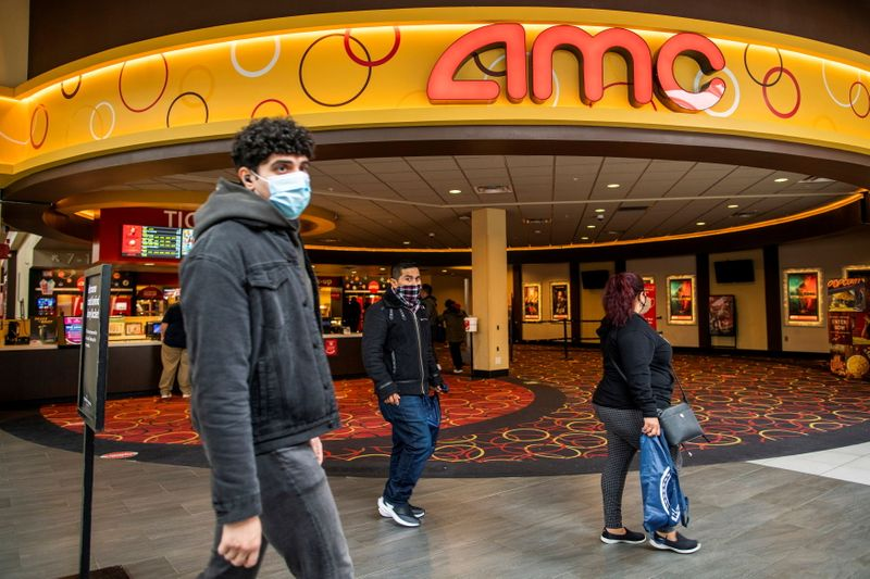 FILE PHOTO: People wear face masks as they walk by a movie theater during the coronavirus disease (COVID-19) pandemic in Newport, New Jersey