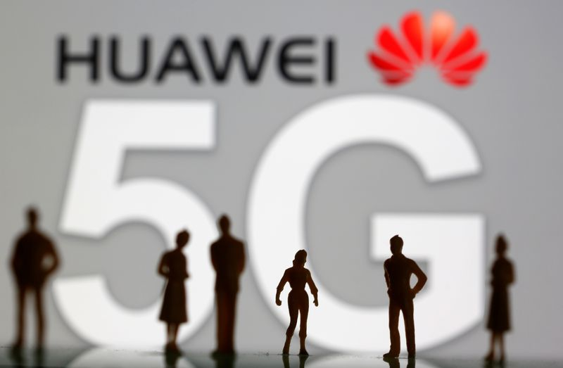 Small toy figures are seen in front of a displayed Huawei and 5G network logo in this illustration picture