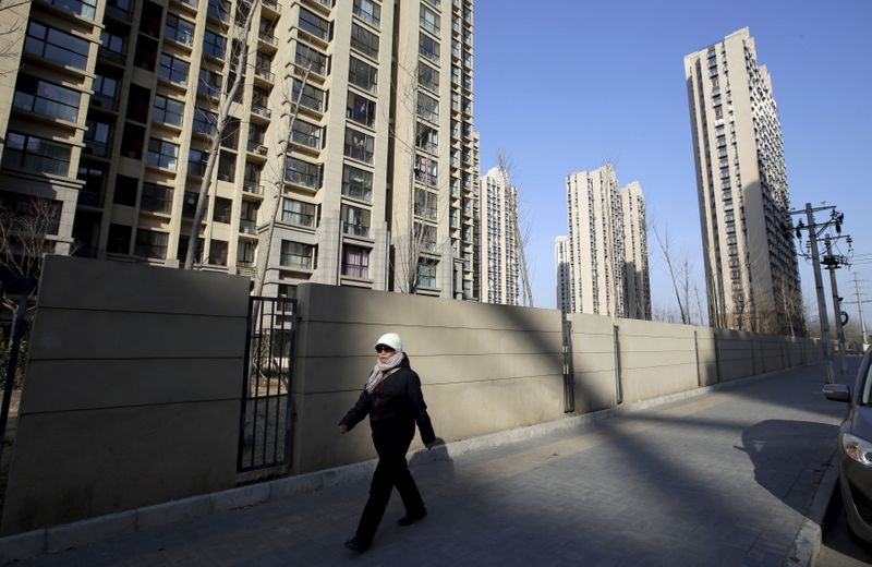 A woman walks past a residential compound in Beijing's Tongzhou district