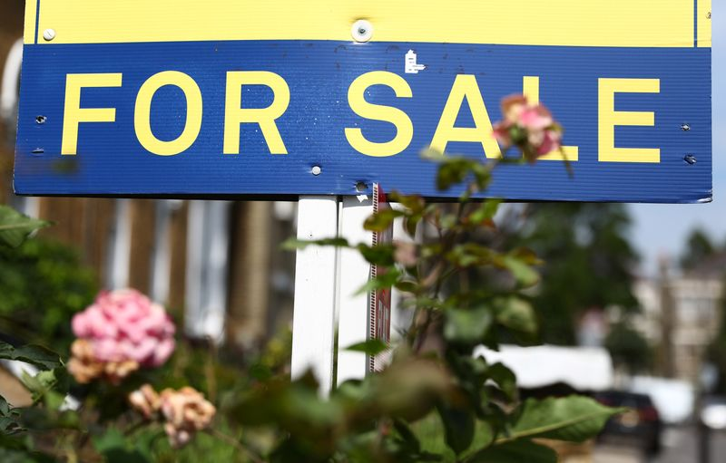 An estate agent board is displayed outside a property in London