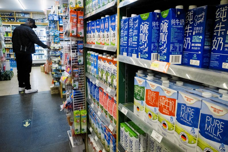 Cartons of milk are displayed on shelves at a supermarket in Beijing