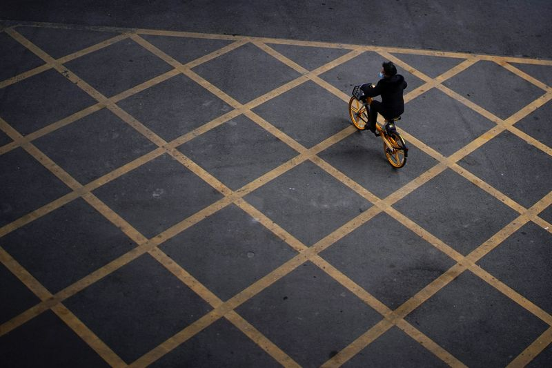 Person wearing a mask rides a bicycle of bike-sharing service on a street, almost a year after the start of the coronavirus disease (COVID-19) outbreak, in Wuhan, Hubei