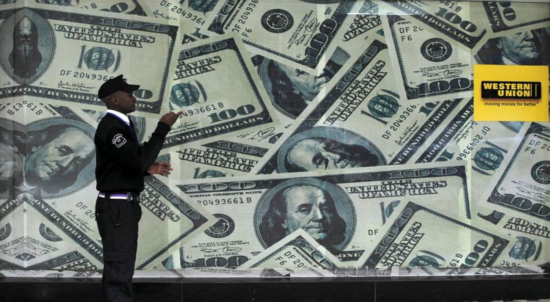 FILE PHOTO: A security guard walks past a montage of old U.S. dollar bills outside a currency exchange bureau ahead of a scheduled State visit by the U.S. President Barack Obama in Kenya's capital Nairobi