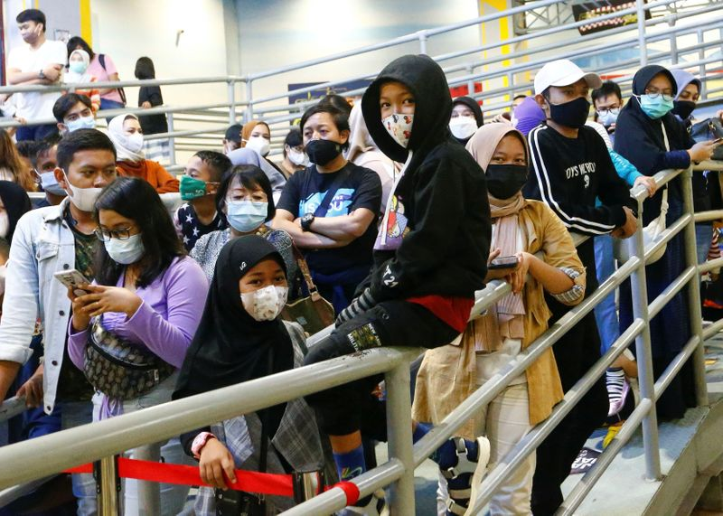 People wearing protective face masks wait for their turn to ride go-karts at Trans Studio, in Jakarta