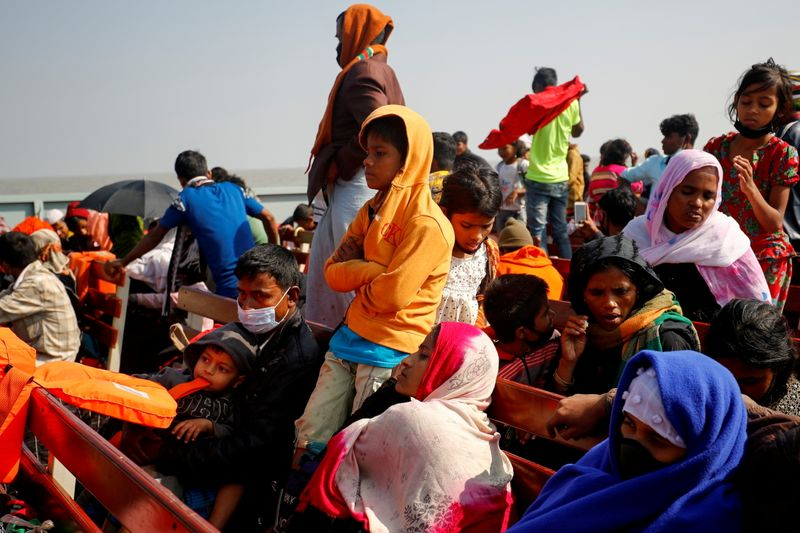 FILE PHOTO: Rohingya refugees sit on wooden benches of a navy vessel on their way to the Bhasan Char island in Noakhali district