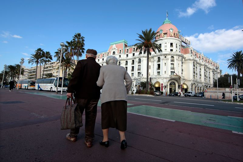 Two elderly people walk on the Promenade Des Anglais in Nice
