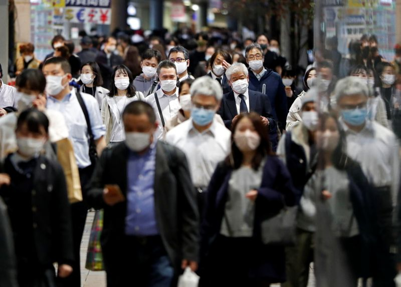 People wearing protective face masks walk on the street, amid the coronavirus disease (COVID-19) outbreak, in Tokyo