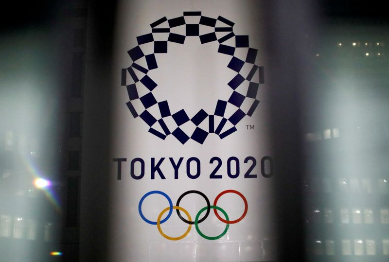 FILE PHOTO: FILE PHOTO: The logo of Tokyo 2020 Olympic Games is seen through signboards, in Tokyo