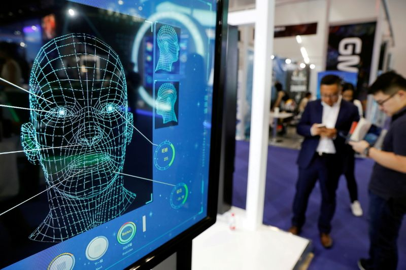 FILE PHOTO: FILE PHOTO: Visitors check their phones behind the screen advertising facial recognition software during Global Mobile Internet Conference (GMIC) at the National Convention in Beijing