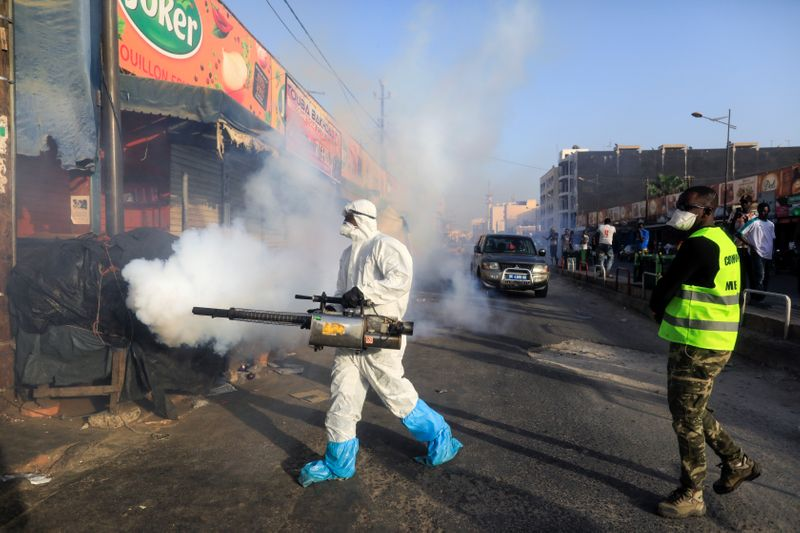 FILE PHOTO: A member of local hygiene services wears a protective suit and a face mask as he disinfects the street and market to stop the spread of coronavirus disease (COVID-19) in Dakar