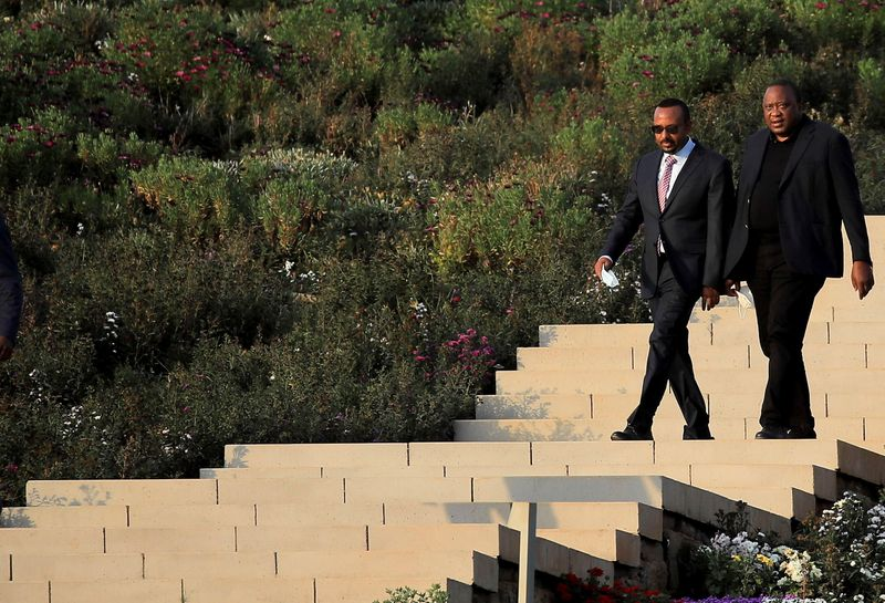 Ethiopian Prime Minister Abiy Ahmed and Kenya's President Uhuru Kenyatta arrive to attend the ceremony where Kenyan telecoms firm Safaricom signed the Ethiopian license in Addis Ababa