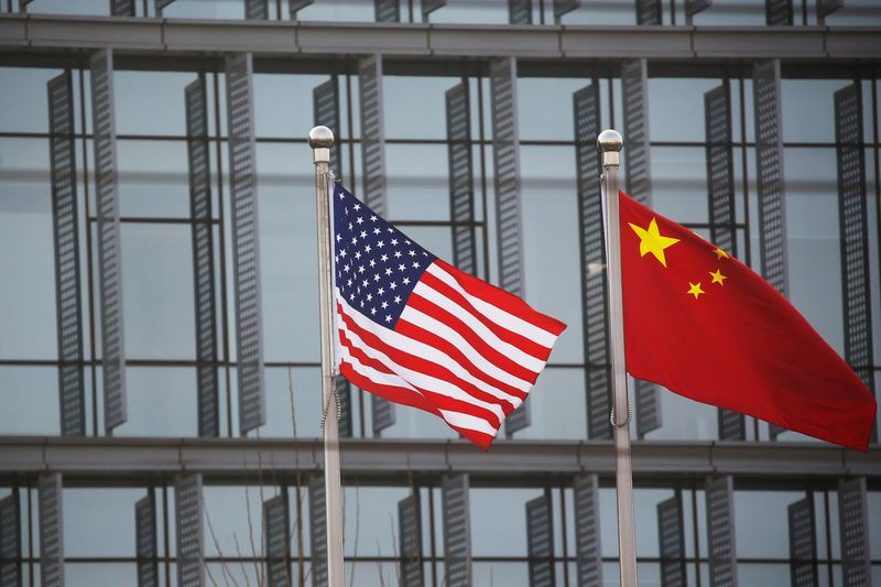 Chinese and U.S. flags flutter outside the building of an American company in Beijing