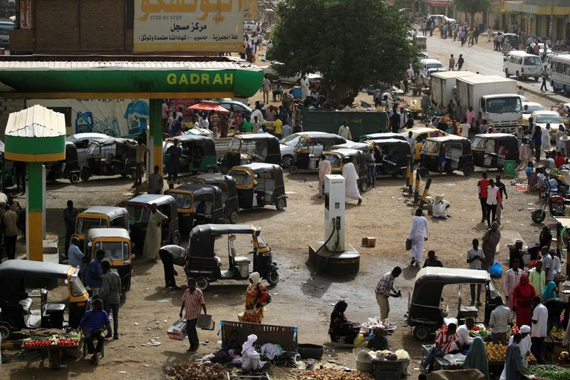 FILE PHOTO: Vehicles line up for gasoline at a gas station in Khartoum