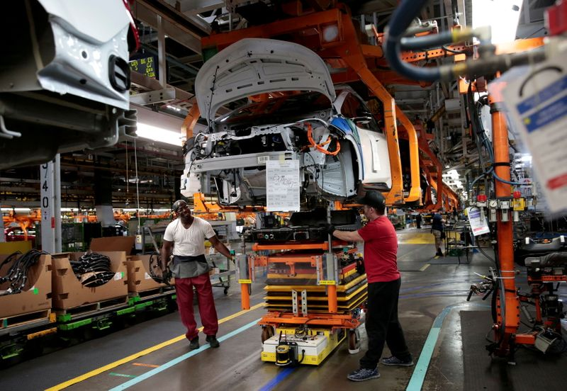 FILE PHOTO: FILE PHOTO: General Motors assembly workers connect a battery pack underneath a partially assembled Chevrolet Bolt EV vehicle