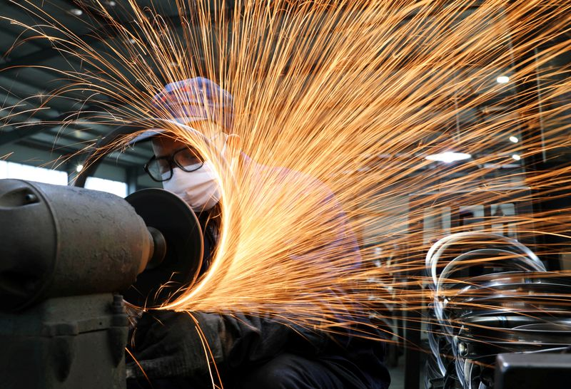 FILE PHOTO: Worker wearing a face mask works on a production line manufacturing bicycle steel rim at a factory in Hangzhou, Zhejiang
