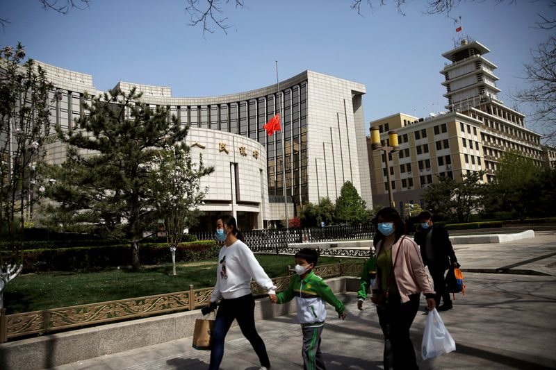 FILE PHOTO: People wearing face masks walk past the headquarters of PBOC