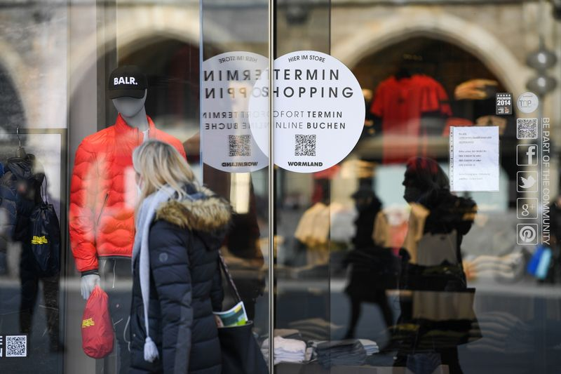 A woman passes a shop with a sticker reading
