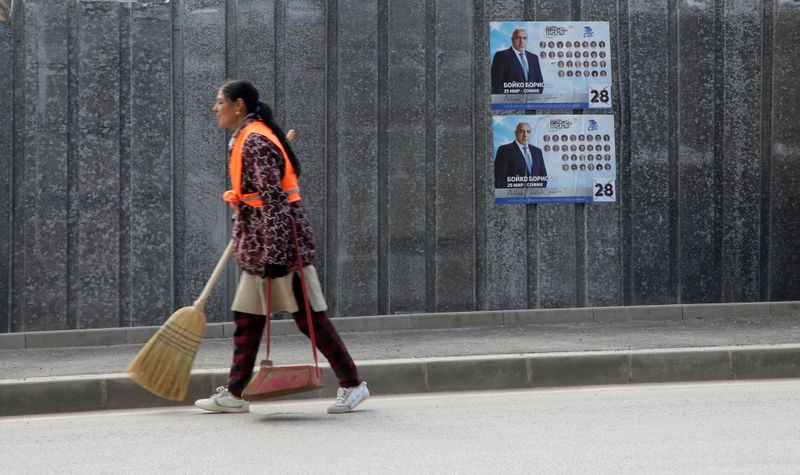 FILE PHOTO: A street cleaner carries a broom near election posters of Boyko Borissov, Bulgarian Prime Minister and leader of centre-right GERB party in Bankya