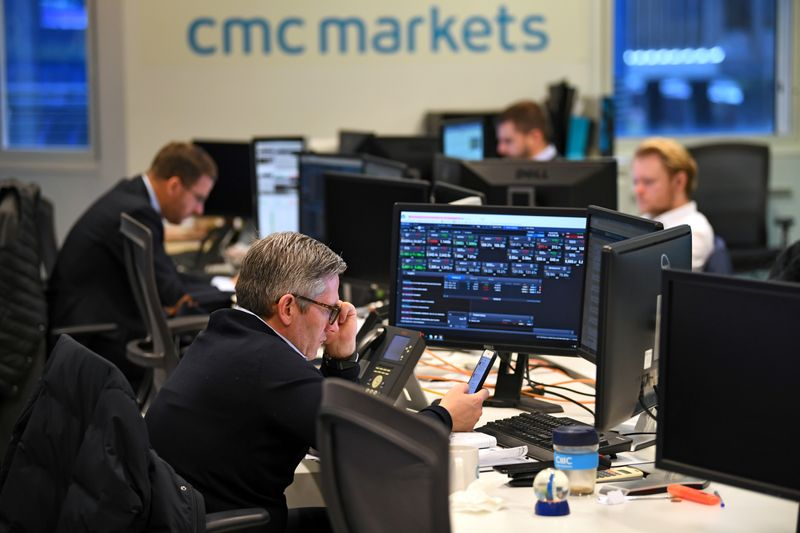 FILE PHOTO: Dealers work at their desks whilst screens show market data at CMC Markets in London