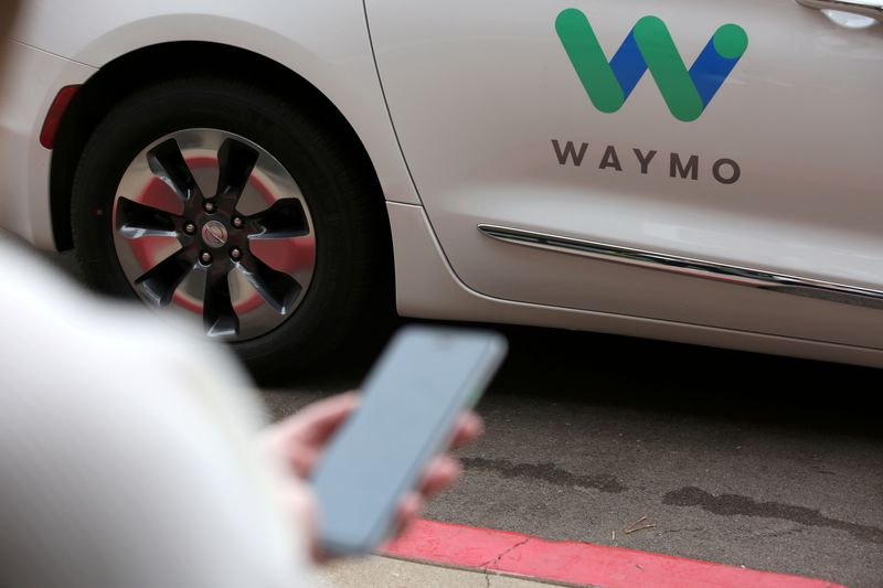 FILE PHOTO: A Waymo employee hails a ride on their phone during a demonstration in Chandler, Arizona
