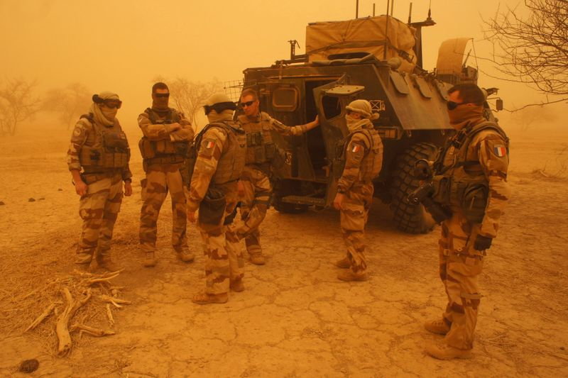 FILE PHOTO: French soldiers from Operation Barkhane stand outside their armored personnel carrier during a sandstorm in Inat
