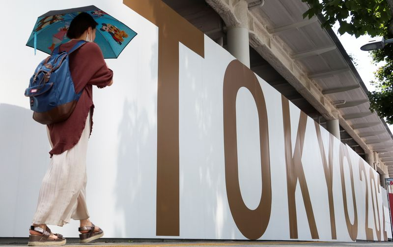 A woman walks outside the security fence of Olympic Stadium (National Stadium) built for Tokyo Olympic Games