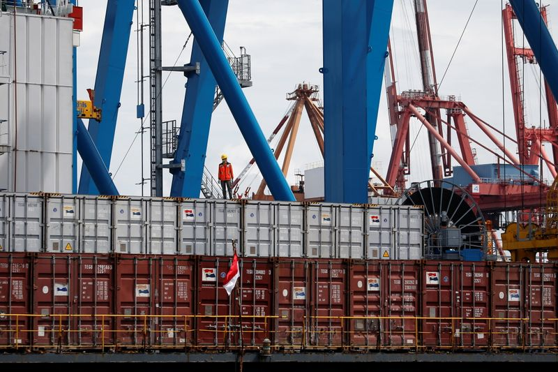 FILE PHOTO: A worker stands on a container at Tanjung Priok Port in Jakarta