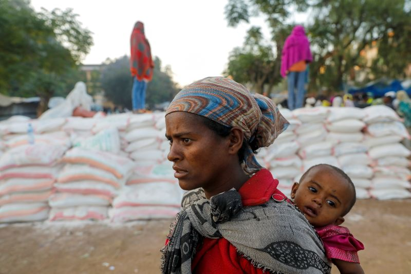Woman carries an infant as she queues in line for food, at the Tsehaye primary school, in Shire