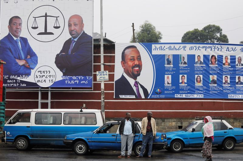 Taxi drivers stand in front of campaign banners ahead of Ethiopia's parliamentary and regional elections in Addis Ababa