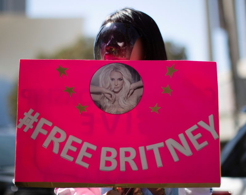 FILE PHOTO: A supporter wearing a personal protective face shield holds a sign while rallying for pop star Britney Spears during a conservatorship case hearing at Stanley Mosk Courthouse in Los Angeles