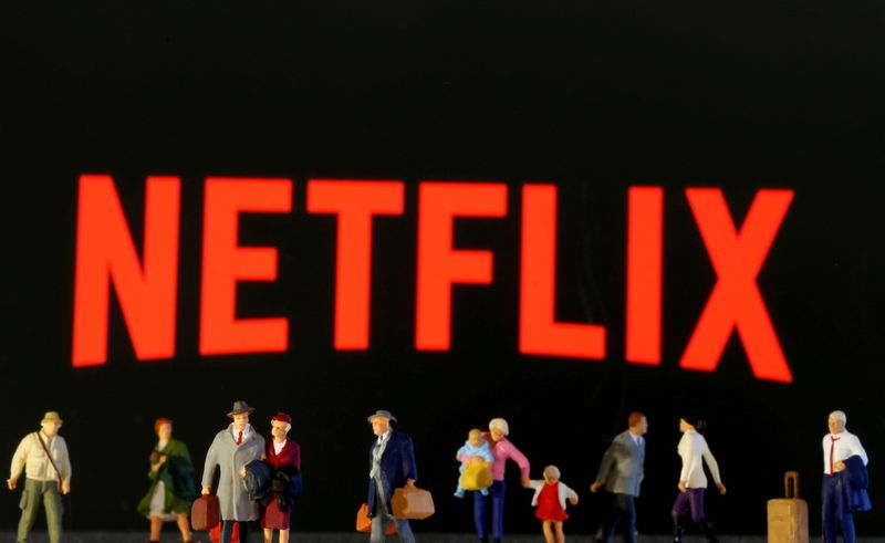 FILE PHOTO: Small toy figures are seen in front of displayed Netflix logo