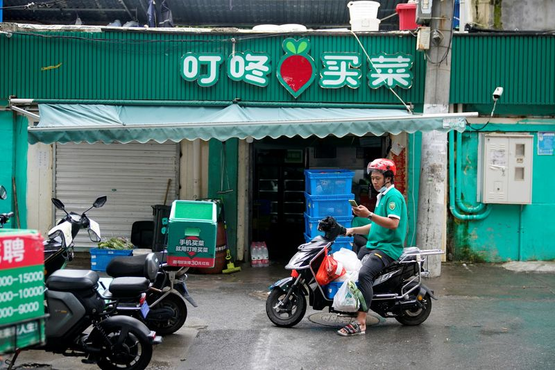 A delivery worker of Chinese online grocery Dingdong Maicai works at a shop on a street in Shanghai