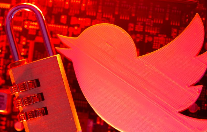 FILE PHOTO: A 3D printed Twitter logo and a padlock on a computer motherboard