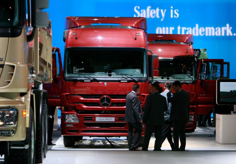 Visitors stend in front of a display of Daimler trucks during a preview day at the IAA commercial vehicles trade fair in Hanover