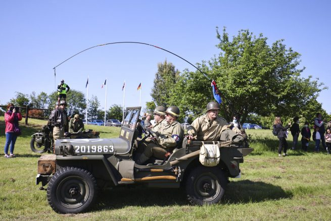 World War II history enthusiasts parade in WWII vehicles in Colleville-Montgomery, Normandy, Saturday June, 5 2021 on the eve of 77th anniversary of the assault that helped bring an end to World War II. (AP Photo/David Vincent)