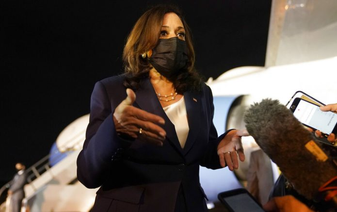 Kamala Harris talks to the press gathered under the wing of Air Force Two. (AP Photo/Jacquelyn Martin)