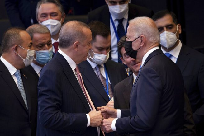 Turkey's President Recep Tayyip Erdogan, center left, greets U.S. President Joe Biden, center right, during a plenary session during a NATO summit at NATO headquarters in Brussels, Monday, June 14, 2021. U.S. President Joe Biden is taking part in his first NATO summit, where the 30-nation alliance hopes to reaffirm its unity and discuss increasingly tense relations with China and Russia, as the organization pulls its troops out after 18 years in Afghanistan. (Brendan Smialowski, Pool via AP)
