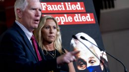 """A poster that reads """"Fauci lied. People died."""" is visible next to Rep. Mo Brooks, R-Ala., left, accompanied by Rep. Marjorie Taylor Greene, R-Ga., as he speaks during a news conference about Taylor Greene's bill to audit the correspondence and financial statements of Dr. Anthony Fauci, director of the National Institute of Allergy and Infectious Diseases on Capitol Hill in Washington, Tuesday, June 15, 2021. (AP Photo/Andrew Harnik)"""