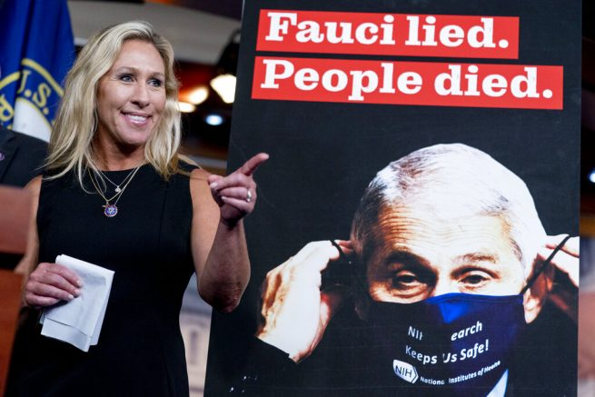 """A poster that reads """"Fauci lied. People died."""" is visible next to Rep. Marjorie Taylor Greene, R-Ga., as she takes a question during a news conference about her bill to audit the correspondence and financial statements of Dr. Anthony Fauci, director of the National Institute of Allergy and Infectious Diseases on Capitol Hill in Washington, Tuesday, June 15, 2021. (AP Photo/Andrew Harnik)"""