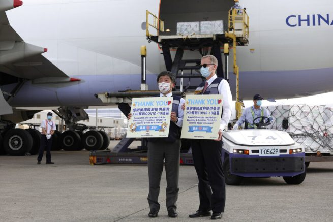 In this photo released by the Taiwan Centers for Disease Control, Taiwan's Health Minister Chen Shih-chung, left, and Brent Christensen, the top U.S. official in Taiwan, hold up thank you cards as they welcome a China Airlines cargo plane carrying COVID-19 vaccines from Memphis. (Taiwan Centers for Disease Control via AP)
