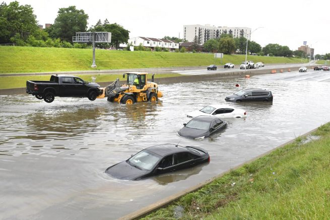 A truck is hoisted from a flooded I75 and Canfield Street as heavy rain flooded streets in the metro area of Detroit. (Max Ortiz/Detroit News via AP)