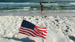 GULF SHORES, AL - JULY 04: An American flag is stuck in the sand along a beach which was not as busy as last year as people stayed away due to the threat of contamination from the Deepwater Horizon oil spill in the Gulf of Mexico on July 4, 2010 in Gulf Shores,Alabama. The oil spill may have a huge negative economic impact on gulf coast businesses during what should be a busy 4th of July. Millions of gallons of oil have spilled into the Gulf since the April 20 explosion on the drilling platform. (Photo by Joe Raedle/Getty Images)
