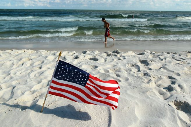 An American flag is stuck in the sand along a beach in Gulf Shores, Ala. (Photo by Joe Raedle/Getty Images)